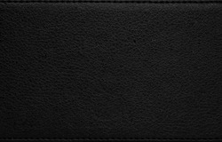 Black leather texture. Dark synthetic material background. Detail of rough surface.