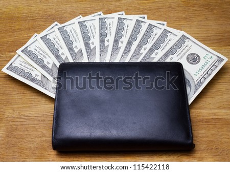 black leather wallet with money on wooden background