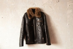 black leather winter mens jacket hanging on a hanger on the wall