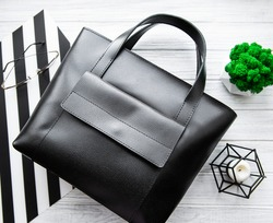 Black leather women's bag. Flat lay. Top view.