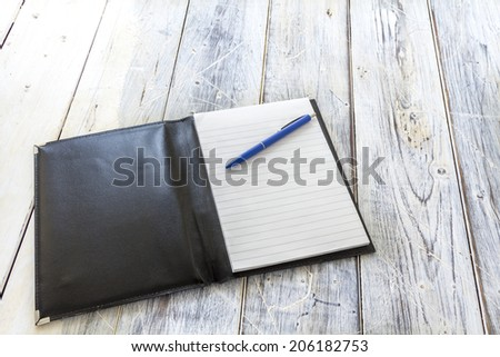 black leather wrapper with a block and blue pen on a rustic wooden table
