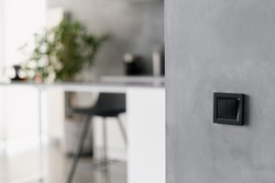 Black light switch on grey wall in modern themed kitchen environment, black bar stool, various home appliances, different white furniture and potted plant in blurred background
