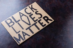 BLACK LIVES MATTER. No racism concept on a dark background. Cardboard banner with a text