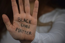 Black Lives Matter written on long haired white woman's hand. Caucasian girl  against racism and police brutality. Support to African Americans.