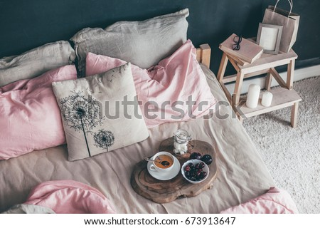 Black loft bedroom and pastel bedding set. Unmade bed with breakfast and reading on tray. Interior decor over blackboard wall. Cozy modern living space. #673913647