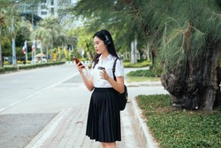 Black long hair college girl in uniform standing on footpath at roadside holding hot coffee and listening the recorded lecture before class.