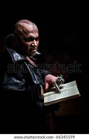 Black Magician in the leather raincoat is reading a book.