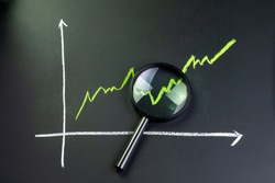 Black magnifying glass on chalk drawing green line stock or company performance graph and chart on blackboard using as financial analysis, profit and loss or searching for earning and yield.