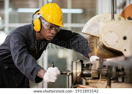 Black male african american workers wear sound proof headphones and yellow helmet working an iron cutting machine in factory Industrial.