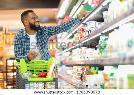 Black Male Buyer Shopping Groceries In Supermarket Taking Dairy Product From Shelf Standing With Shop Cart Indoors. Guy Buys Grocery Choosing Food In Super Market. Empty Space Photo stock ©