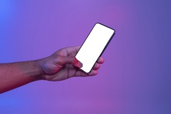 Black Male Hand Holding Smartphone With Glowing White Screen Under Neon Light Over Purple Background, Unrecognizable African American Man Showing Free Copy Space For Your App Design, Mockup Image