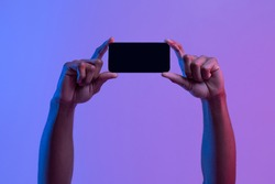 Black Male Hands Holding Smartphone With Black Screen In Horizontal Orientation Under Vivid Neon Light Over Purple Background, Mockup Image With Copy Space For Your App, Game Or Website Design