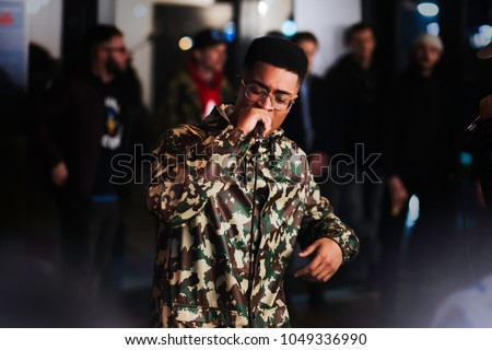 Black male rapping with microphone in camo jacket and glasses. Crowd in background.