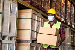 Black male workers wearing protective face mask working in factory warehouse. Black man carrying box parcel walking indoor of building during covid 19 pandemic crisis. Logistic industry concept.