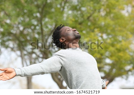 Black man breathing fresh air stretching arms in a park with a green tree in the background