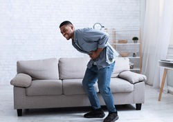 Black Man Having Stomachache Suffering From Painful Abdominal Spasm Standing Touching Aching Abdomen At Home. Abdomen Pain, Stomach Inflammation And Appendicitis Concept