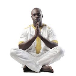 black man meditates sitting on the ground
