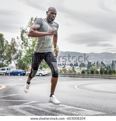 black man running outdoors in...