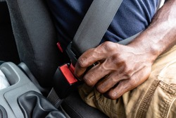 Black man's hand fastens seat belt in car. Buckle your seat belt while sitting inside the car before driving. Closeup shot of male driver fastens seat belt.  for safe journey and auto safety concept