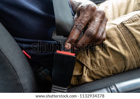 Black man's hand fastens seat belt in car. Buckle your seat belt while sitting inside the car before driving. Closeup shot of male driver fastens seat belt.  for safe journey and auto safety concept - Shutterstock ID 1132934378