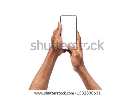 Black man's hands holding mobile phone with blank screen, taking photo on white background, copy space stock photo