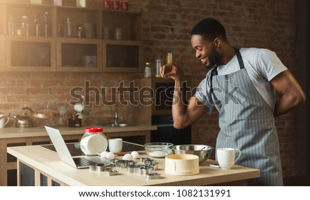 Black man seasoning food at home kitchen. African-american guy in apron baking cookies, adding flaworings to dough and having fun