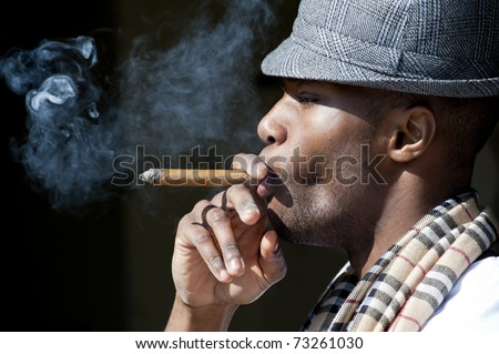 Black man smoking cigar portrait with hat.