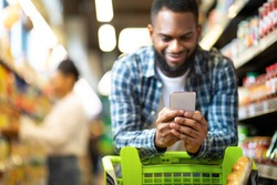Black Man Using Mobile Coupon App For Groceries Shopping Buying Food In Supermarket, Standing With Cart In Hypermarket. African Guy Using Smartphone Purchasing Grocery In Shop. Selective Focus
