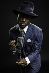 Black man with blue striped suit and blue hat singing. Jazz musician. Night club. Cotton club. New Orleans.