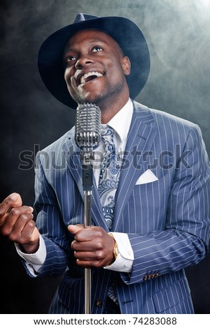 Black man with blue striped suit and blue hat singing. Smoky nightclub like a cotton club