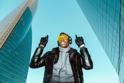Black man with strange and rare yellow sunglasses and headphones. With expression of listening to music. In a office skyscrapers background. Music, electronic music and listening music concept.