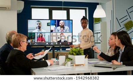 Black manager woman talking with remotely colleagues on video call at tv screen, presenting new business partners. Confident businesswoman talking to web cam streaming webcast training, doing online