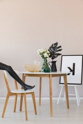 Black mannequin's leg on wooden chair in elegant dining room interior with copy space on the empty wall