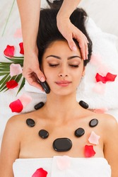 Black marble stone massage in spa. Female patient in wellness center. Professional massagist make relaxation procedure to beautiful indian girl in beauty parlor, top view with rose petals