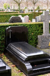 Black Marble tombstones in French cemetery with beautiful crafted crosses and
