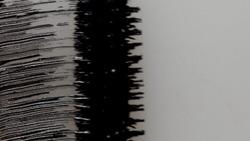 Black mascara brush strokes on white macro texture
