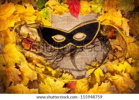 Black masquerade mask and yellow leaves on brown textured background
