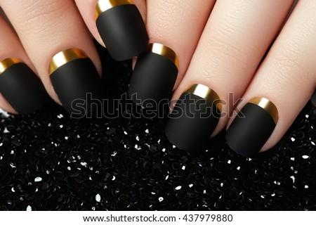 Black matte nail polish. Manicured nail with black matte nail polish. Manicure with dark nailpolish. Golden nail art manicure
