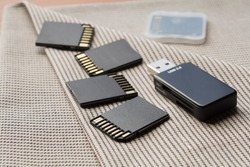 Black memory cards and card reader on textile background
