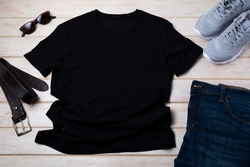 Black men's cotton T-shirt mockup with gray running shoes, dark denim jeans, sunglasses and brown leather belt. Design t shirt template, tee print presentation mock up