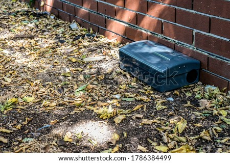 Photo of  Black Metal external rodent rat bait station outside against a brick wall close up.  Pest Control.