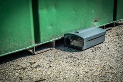 Black Metal external rodent rat bait station outside against a metal container wall close up.  Pest Control.