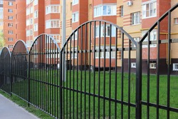 black metal fence in front of urban apartment building