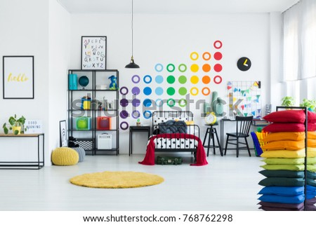 Black metal frame with pile of rainbow pillows standing in a white room with colorful circles on the wall #768762298