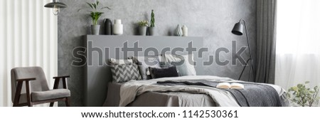 Black metal lamp standing next to double bed with grey sheets in monochromatic bedroom interior with fresh plants, armchair and window with drapes #1142530361