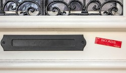 Black metal letterbox screwed onto a beige door with wrought iron. On the right a red label stuck indicates no ads, thank you. Minimalist color photography.