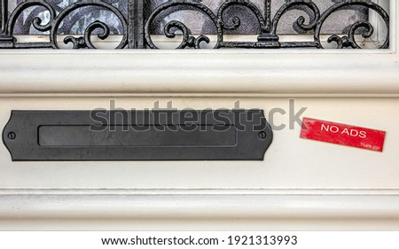 Black metal letterbox screwed onto a beige door with wrought iron. On the right a red label stuck indicates no ads, thank you. Minimalist color photography. Stock photo ©