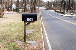 Black metal mailbox number 159 before Glenside Ave in Scotch Plains, New Jersey. Empty street. Cold winter. No traffic, no cars.