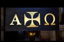 black metal panel with the Greek cross and the letters alpha and omega in gold, symbol of the beginning and the end in Christianity, in the Monastery of Leyre