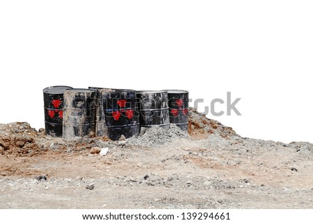Black metal storage drums with radioactive symbol buried on a dilapidated waste storage site, isolated against white for the concept of dangerous toxic waste.